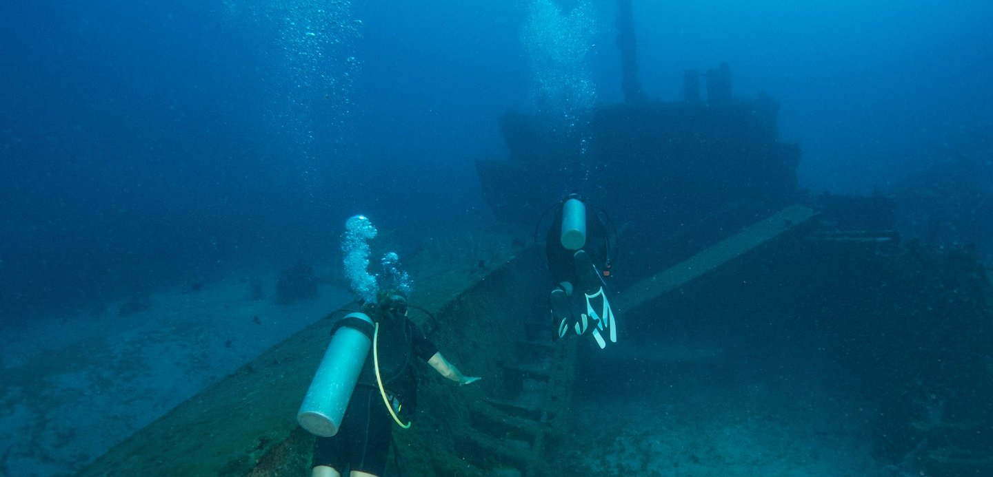 people diving in ship wreck