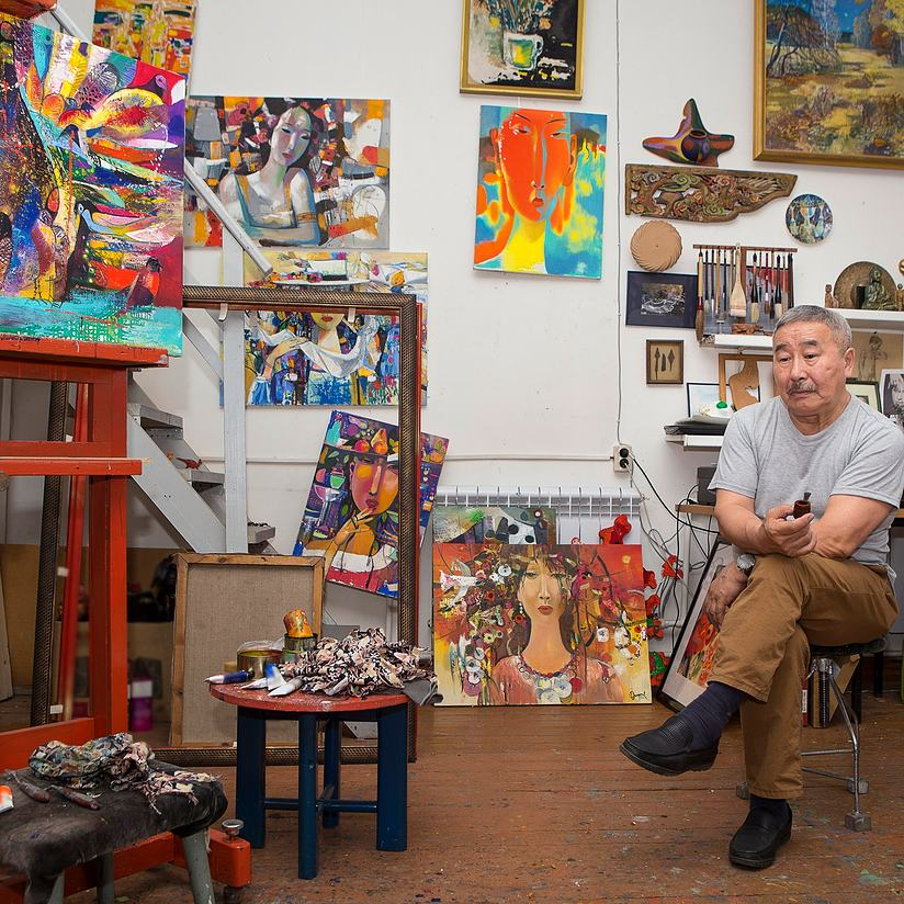 artist posing with his paintings