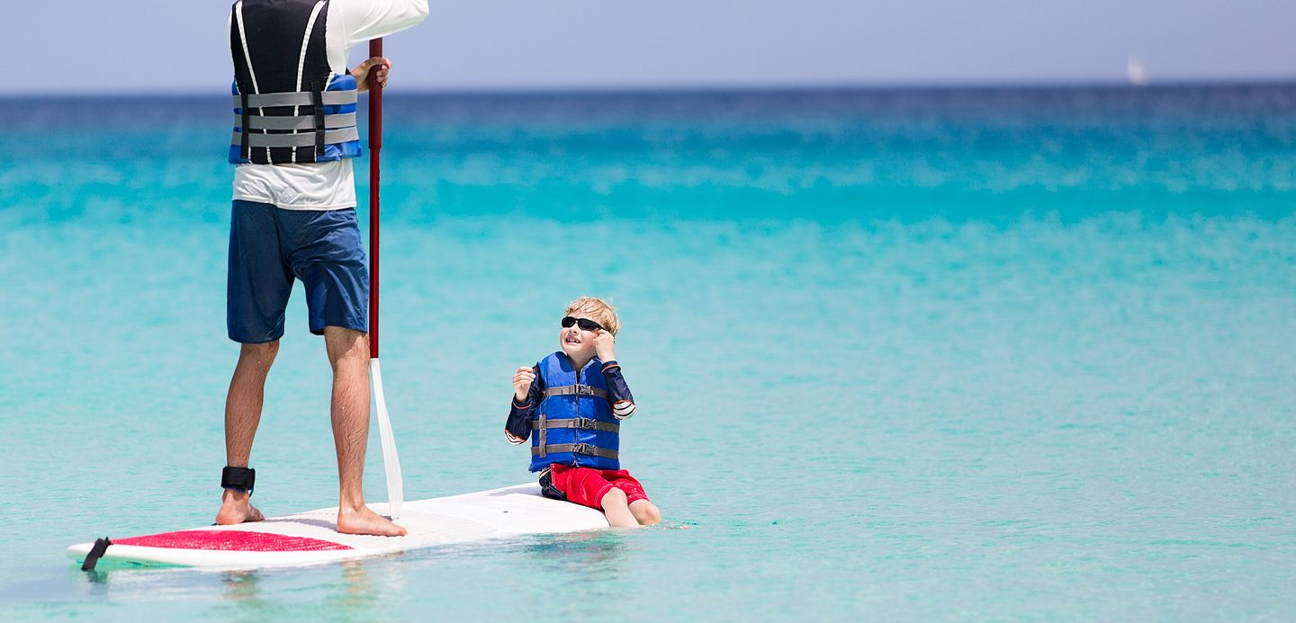 dad and son on a paddle board